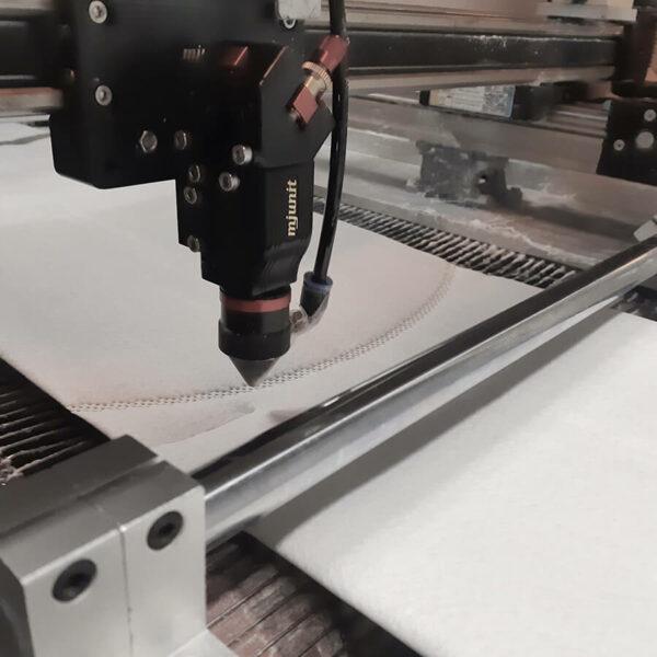 detalhe da máquina efetuando o corte a laser durante a fabricação do filtro bag