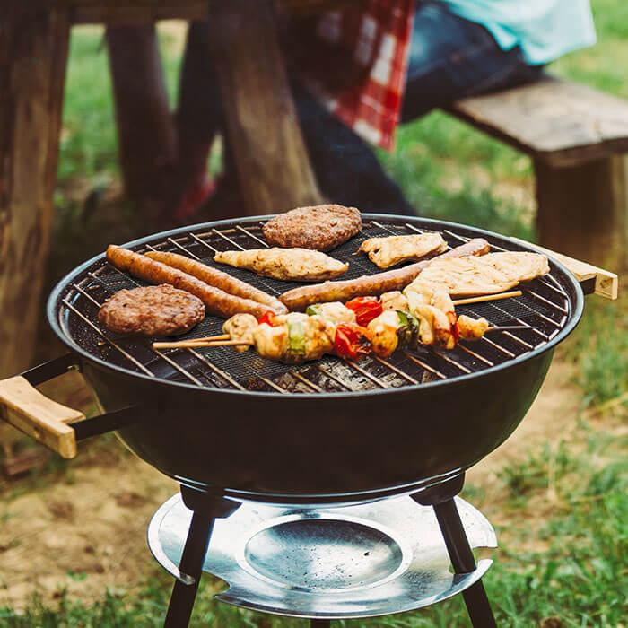 churrasco sendo preparado em um churrasqueira móvel que utiliza a tela grill antiaderente na superfície da gralha
